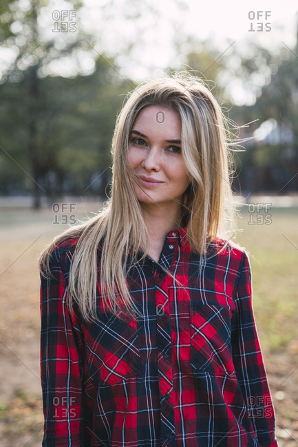 Portrait of blond young woman wearing plaid shirt in autumn
