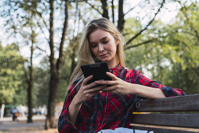 Young woman sitting on bench outdoors using mini tablet