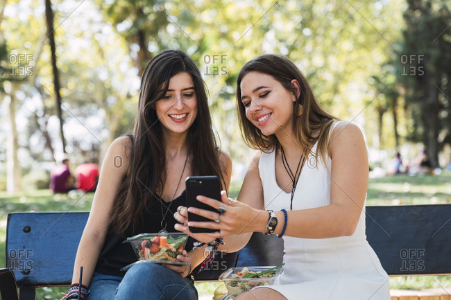 Girl friends sitting on a park bench looking at smartphone