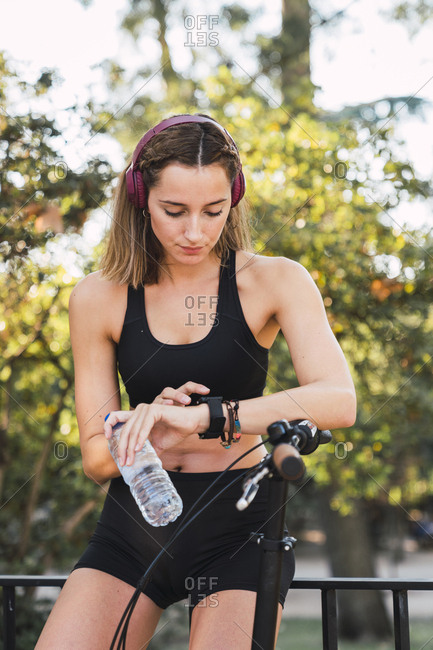 Fit young woman taking a break- holding bottle of water