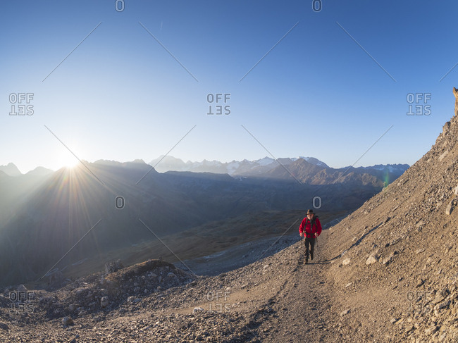 Border region Italy Switzerland- senior man hiking in mountain landscape at Piz Umbrail
