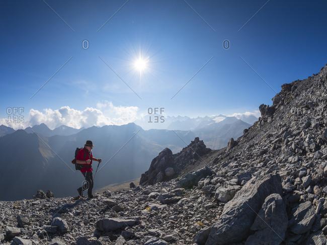 Border region Italy Switzerland- senior man hiking in mountain landscape at Piz Umbrail