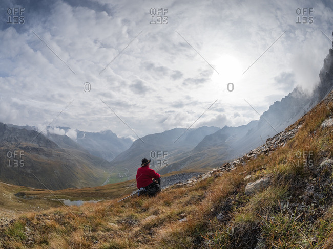 Border region Italy Switzerland- senior man having a break from hiking in mountain landscape at Piz Umbrail