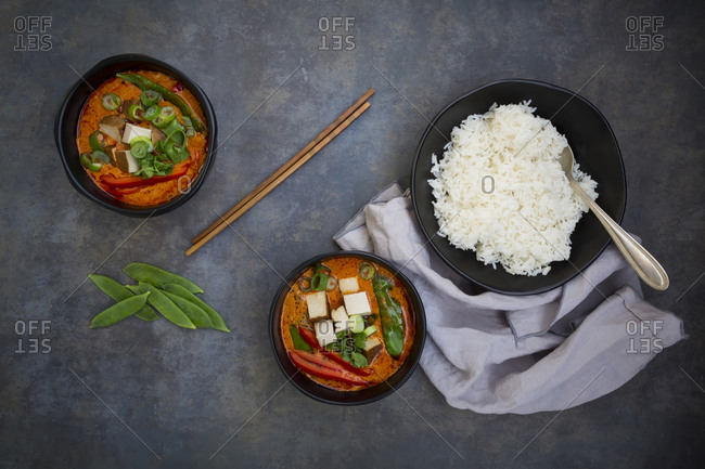 Two bowls of red Thai Curry with snow peas- carrots- bell pepper- spring onions and smoked tofu