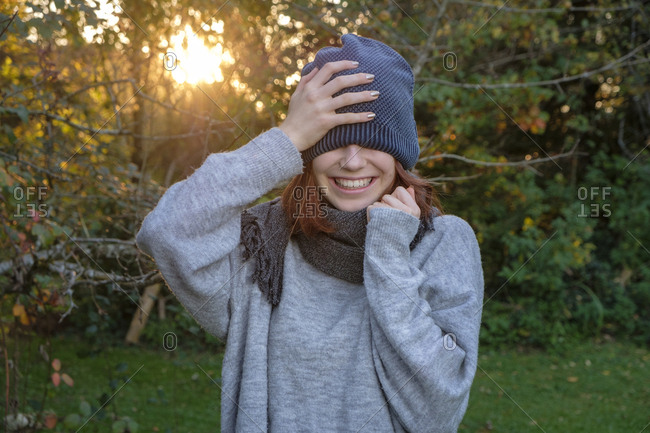 Laughing teenage girl wearing wooly hat and scarf in autumn