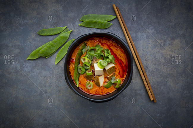Bowl of red Thai Curry with snow peas- carrots- bell pepper- spring onions and smoked tofu