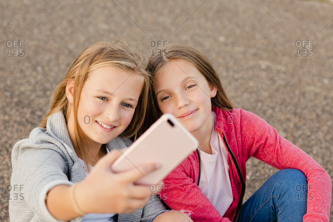 Portrait of two smiling girls taking selfie with smartphone