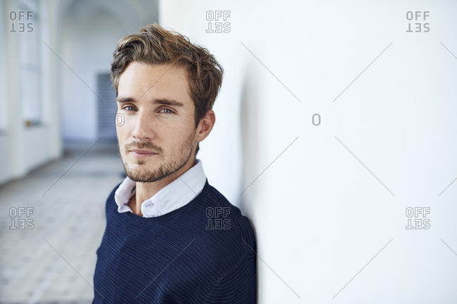 Portrait of sceptical young man leaning against wall