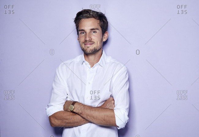 Portrait of content young businessman in front of purple background