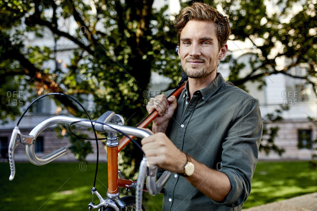 Portrait of smiling young man carrying his racing cycle on shoulder in the city