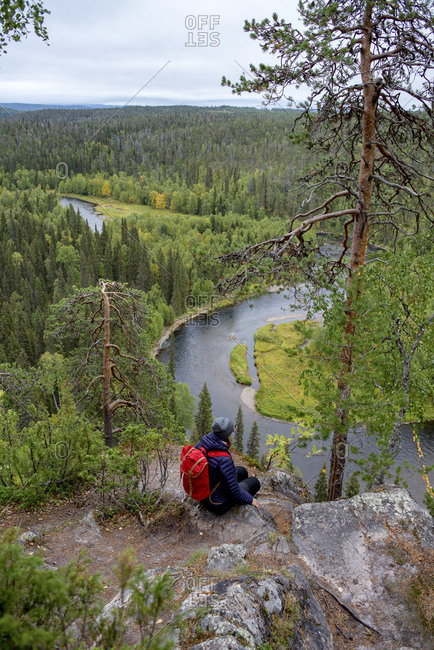 Finland- Oulanka National Park- woman with backpack sitting in pristine nature
