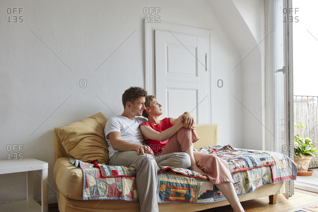 Relaxed couple sitting on couch at home