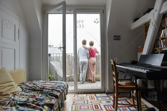 Rear view of couple standing on balcony at home