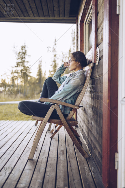 Sweden- Lapland- pensive young woman sitting on chair on veranda looking at distance