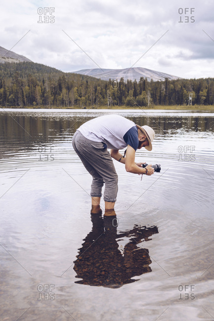 Sweden- Lapland- man standing in water taking photos