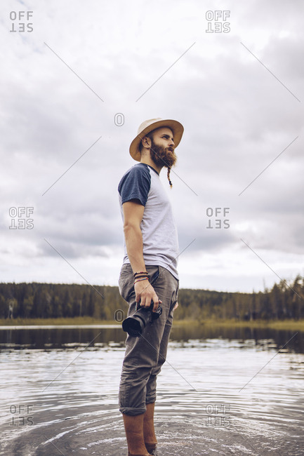 Sweden- Lapland- man with camera standing in water looking at distance
