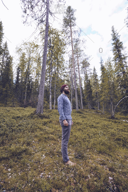 Sweden- Lapland- man standing on forest glade relaxing