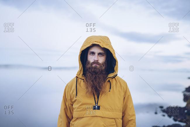 Sweden- Lapland- portrait of serious man with full beard wearing yellow windbreaker