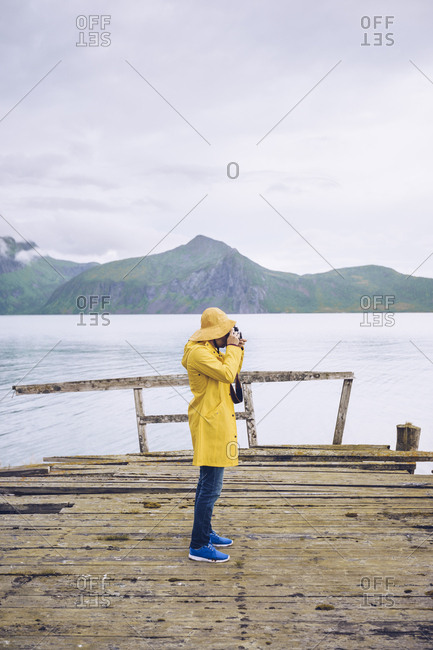 Norway- Senja- man standing on a ramshackle jetty at the coast taking a picture