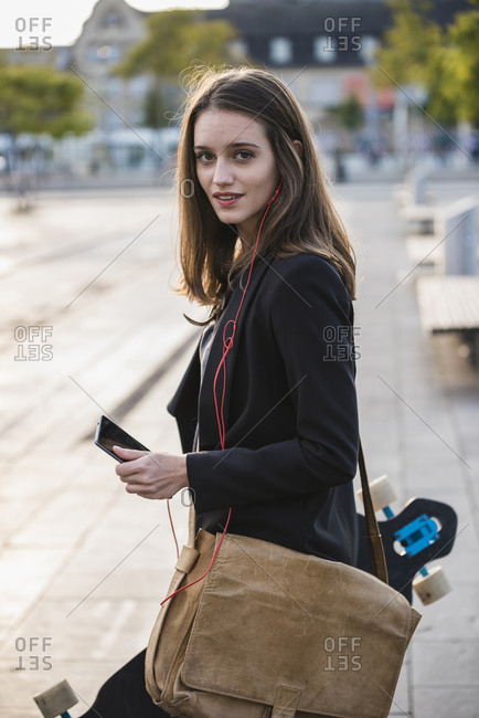 Young woman with longboard and cell phone in the city on the move