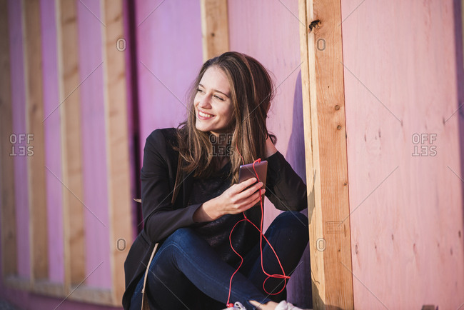 Smiling young woman sitting outdoors listening to music