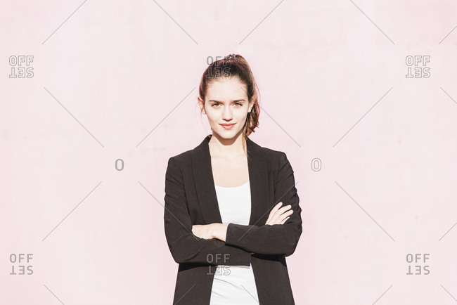 Portrait of confident young woman in front of pink wall