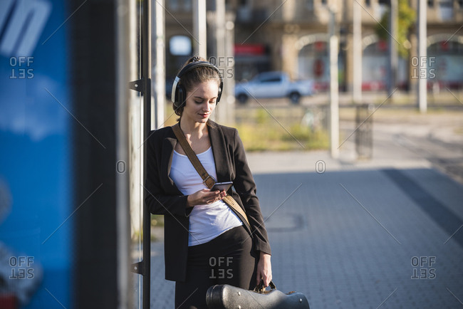 Young woman with headphones and cell phone at tram station