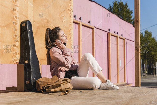 Smiling young woman sitting on platform next to guitar case listening to music