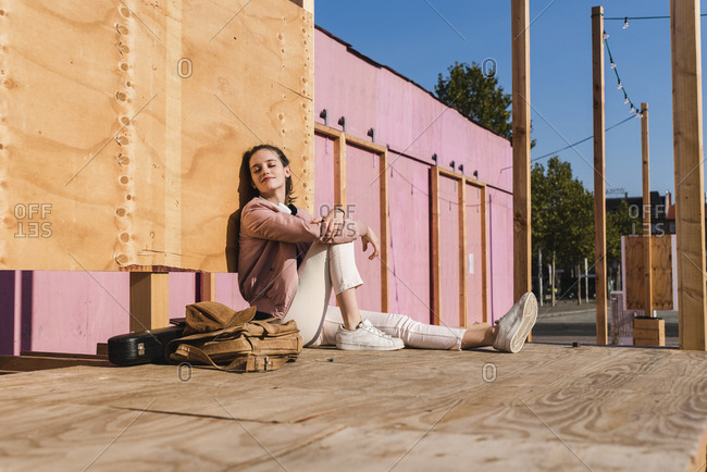 Relaxed young woman sitting on platform next to guitar case and bag