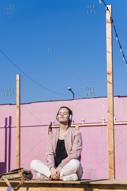 Relaxed young woman sitting on platform listening to music