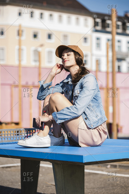 Relaxed young woman sitting on table tennis table listening to music
