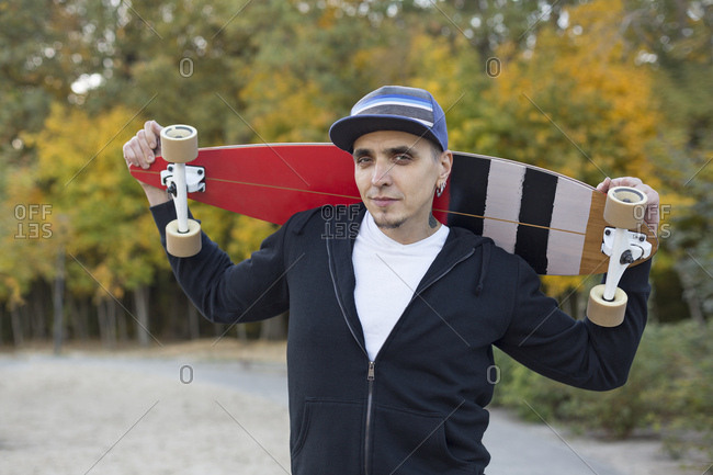 Portrait of man with skateboard on shoulders in autumn