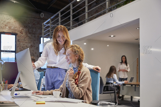 Young woman working in modern creative office- colleague giving advice