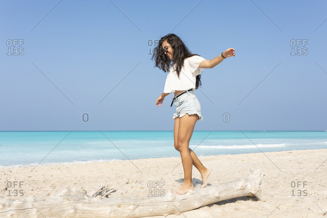 Young woman on the beach balancing on a tree trunk