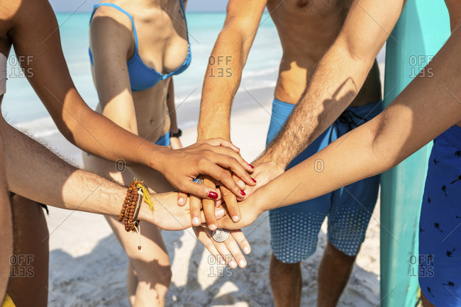 Group of friends on the beach stacking hands