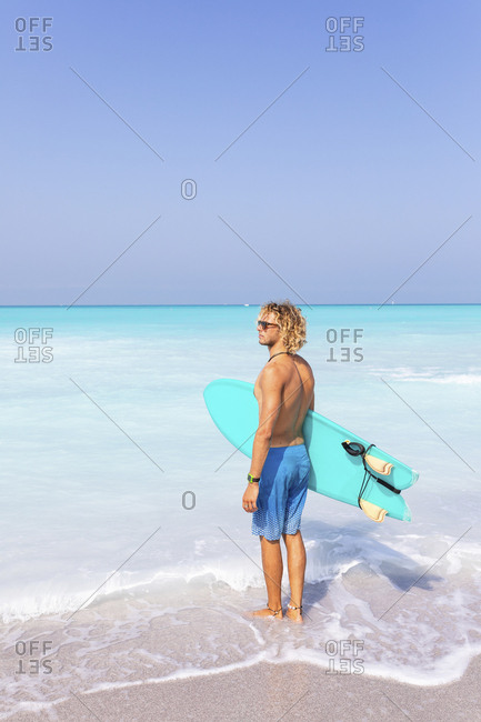 Young man standing at the sea- holding his surfboard