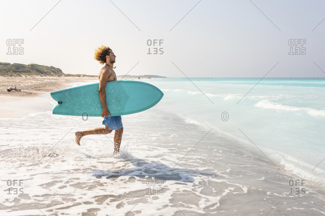 Young man running into ghe sea- carrying his surfboard