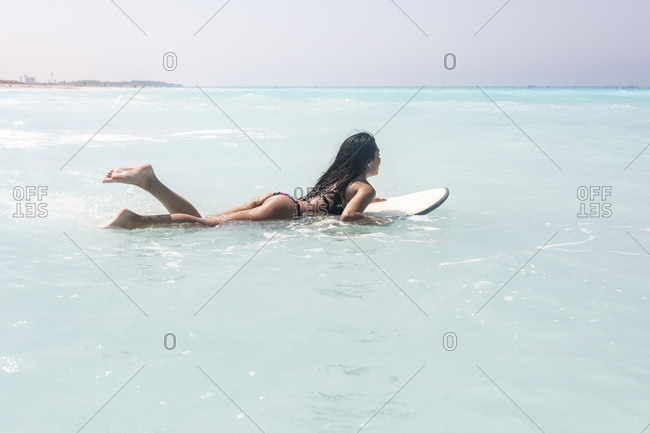 Young woman lying on surfboard- floating on the sea
