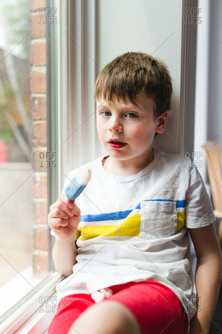 Boy sitting in a windowsill eating an ice pop