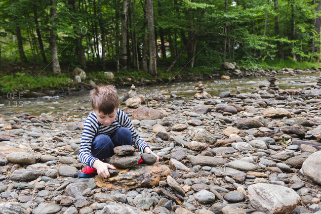 Child stacking rocks along a riverbank