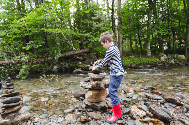 Boy stacking a tall pile of rocks along a river