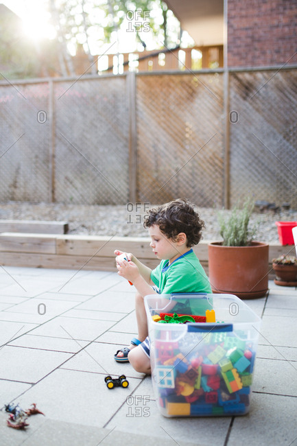 Boy with a box of toys on the patio