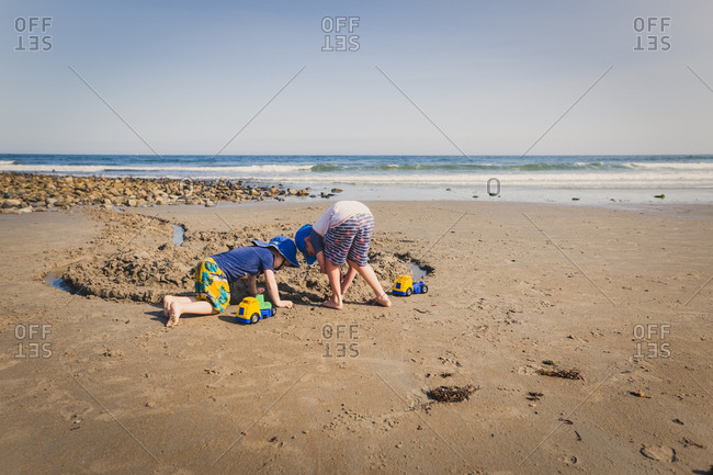 Children digging in sand at the beach
