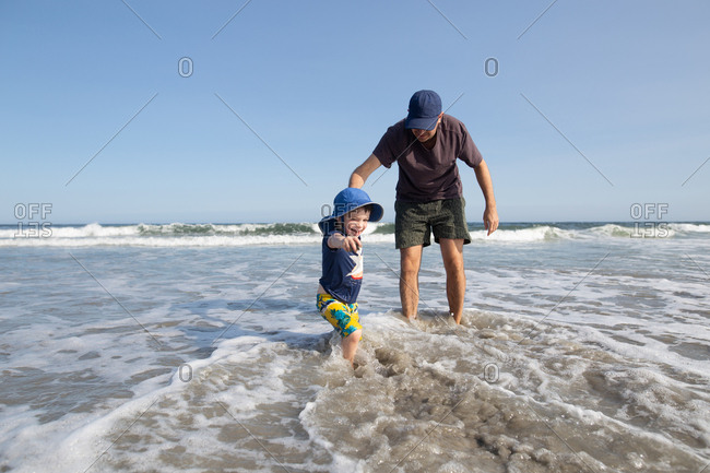 Father and son wading in the ocean waves at the beach