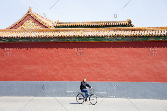 Beijing, China - March 22, 2016: Man riding a bicycle through the Forbidden City palace complex in Beijing, China