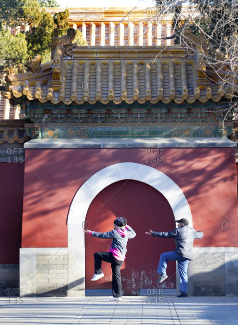 Beijing, China - March 24, 2016: Married couple doing morning Tai Chi in a park next to the Forbidden City palace complex