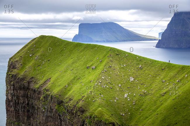 Hiker over a cliff in Kalsoy, Faroe Islands, Europe