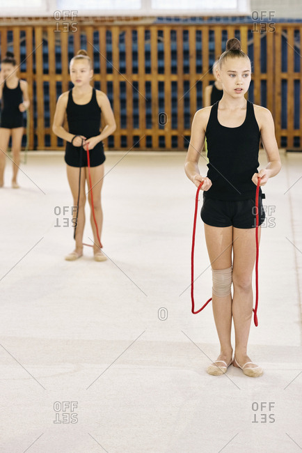 Athletic Caucasian little girls wearing black uniform training with skipping ropes during gymnastics class at school