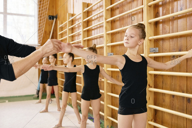 Pretty little female dancers training near gymnastics ladder at sports hall while having ballet class with professional teacher