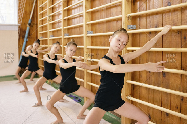 Caucasian little girls doing choreographic exercises near wall bars at school gymnasium while having rhythmic gymnastics class